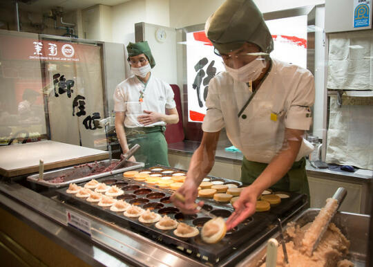 Worker flipping taiyaki