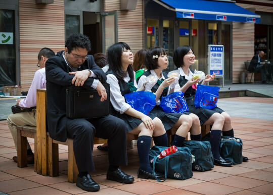 Schoolchildren and a businessman sharing a bench