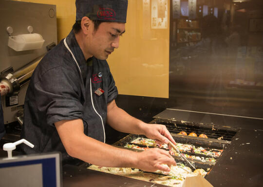 Worker making takoyaki