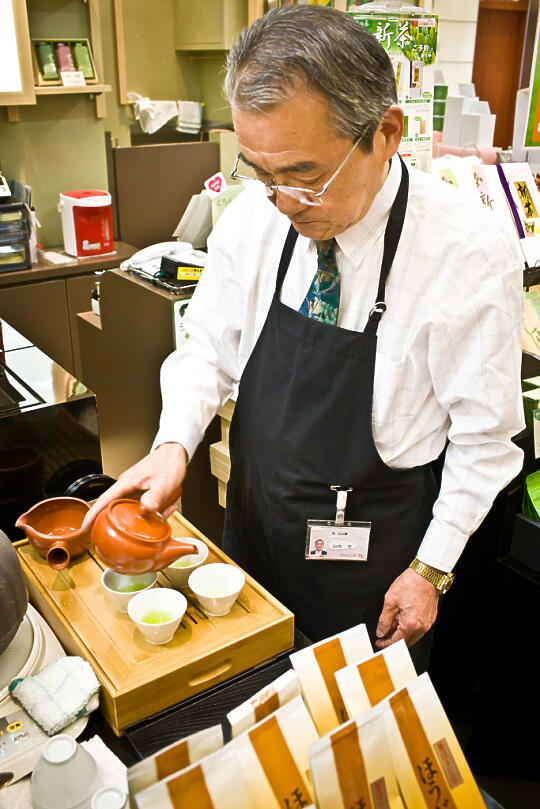 Old man preparing green tea in mall