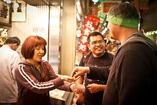 Brian and Francis buying something at Nishiki Market