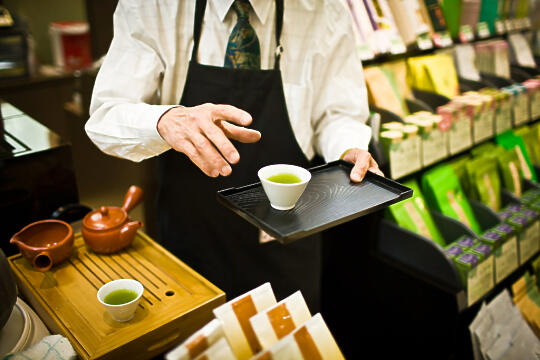 Old man serving us green tea in mall