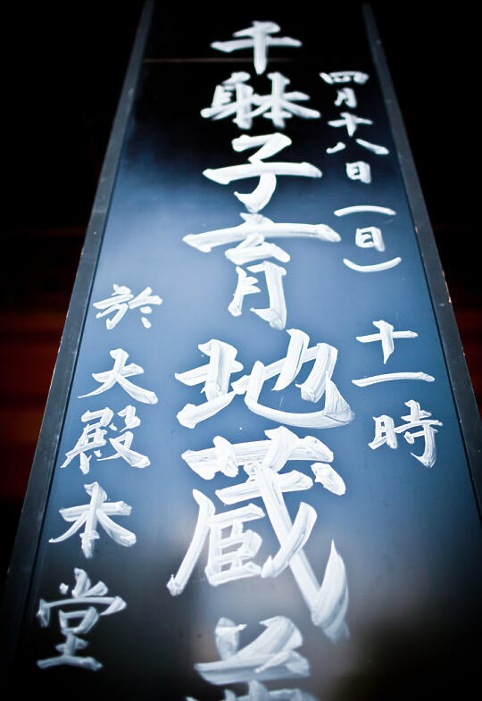 Black placard with white Japanese writing at the temple