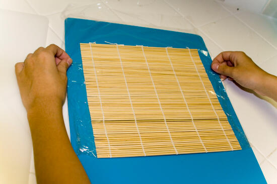 Folding the plastic wrap over the bamboo mat