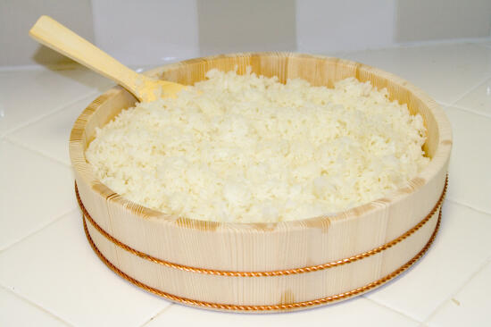 Sushi rice in a wooden hangiri (a large, flat, round container)