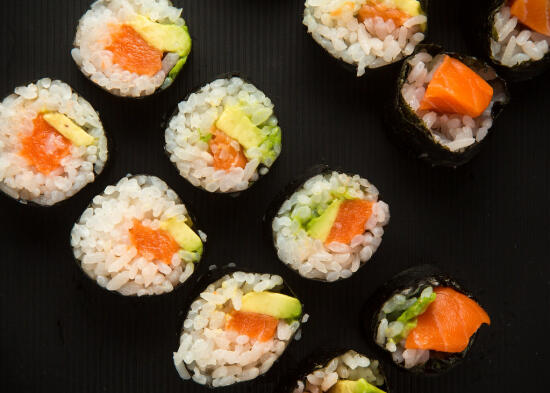 Salmon and avocado maki rolls on a black plate